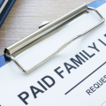 A request form attached to a clipboard that says paid family leave across the top.