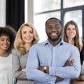 A diverse office staff smiling into the camera with their arms crossed.