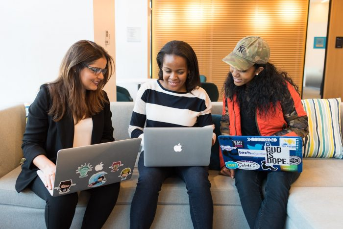 multiracial group of three women at work, on a couch with their laptops, happily in conversation